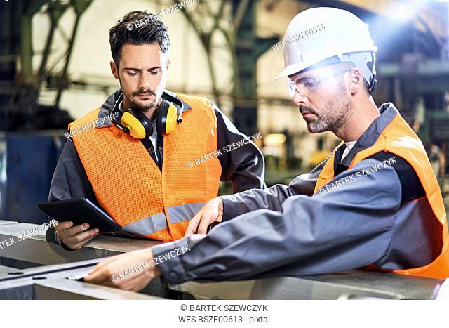 Two men wearing protective workwear working in factory