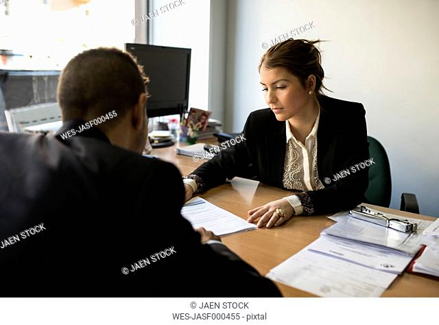 Man and woman in office sitting opposite looking at document