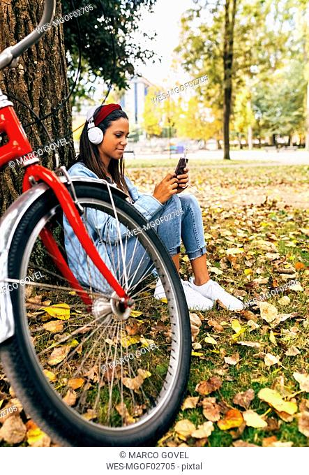 Young woman listening to music with her smartphone in a park in autumn