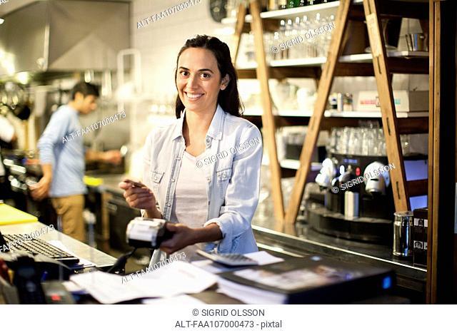 Woman using credit card reader at restaurant
