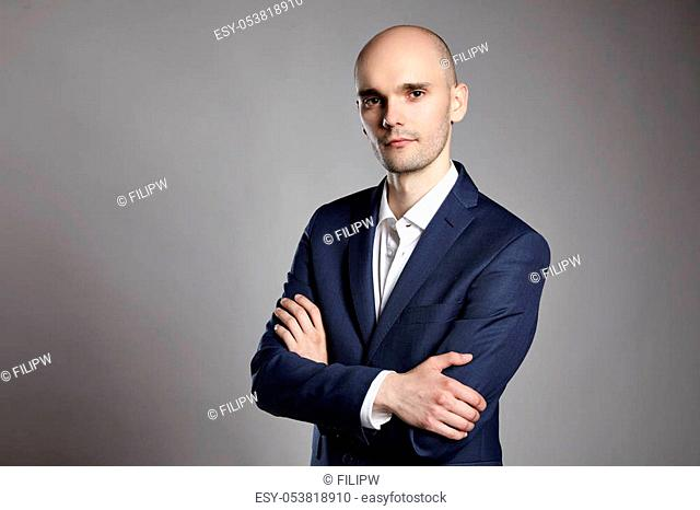 Portrait of young pensive businessman on gray background