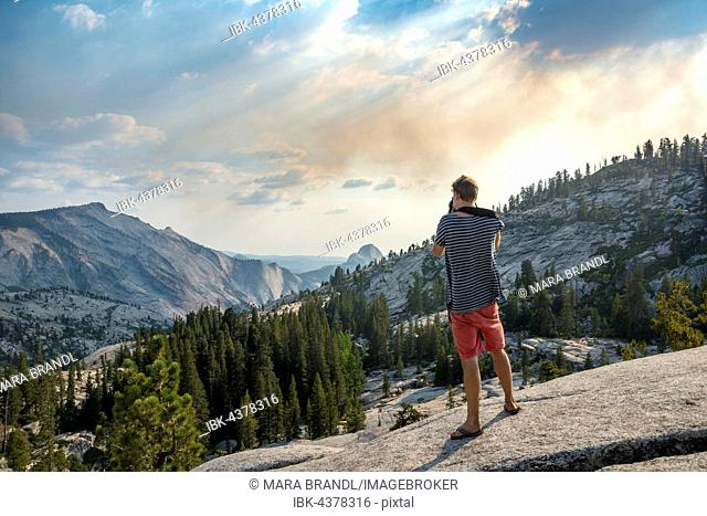 Young man, tourist photographing High Sierra, Olmsted Point, Yosemite National Park, California, USA
