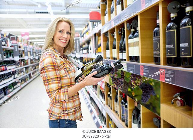 Woman Choosing Wine In Supermarket
