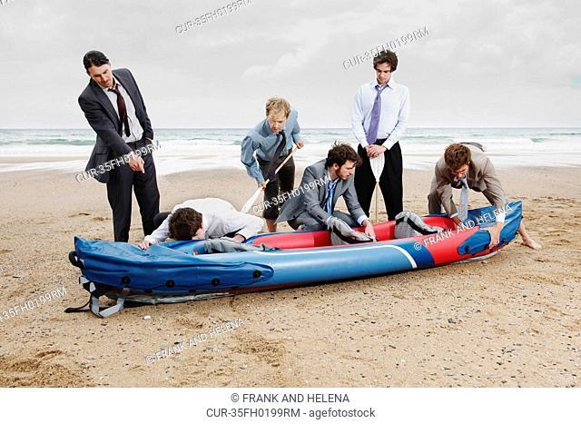 Businessmen with canoe on beach
