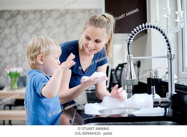 Mother and son doing washing up together