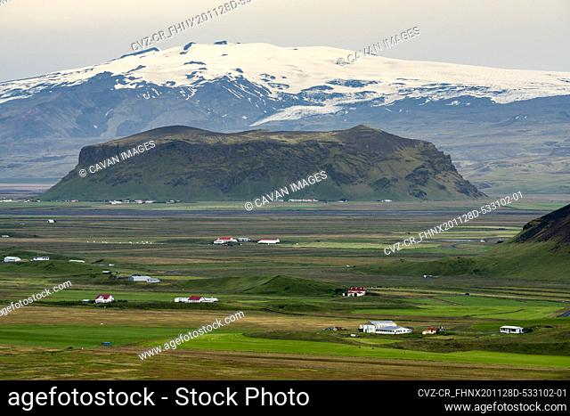 Farmhouses with snowcapped mountains in background, South Iceland
