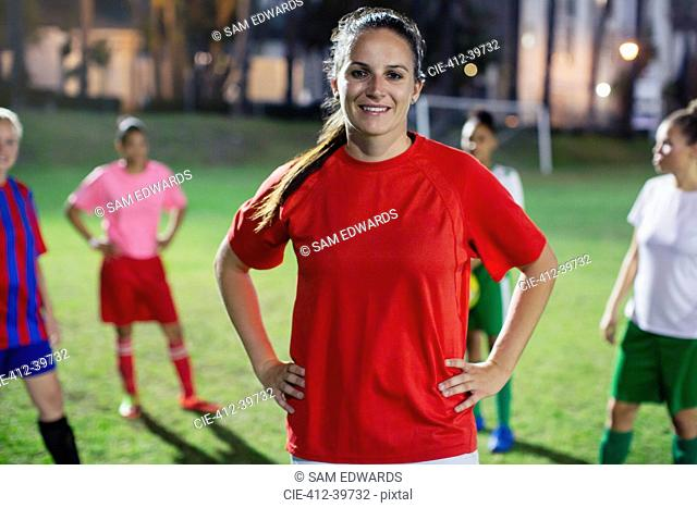 Portrait confident, smiling young female soccer player on field at night