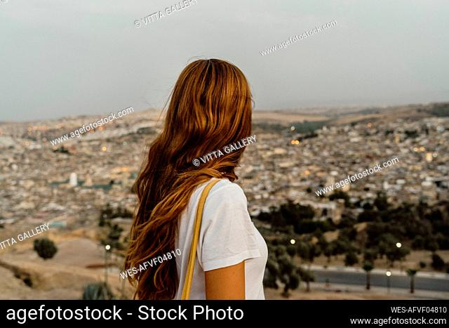 Redheaded woman enjoying city view in the evening, Fez, Morocco
