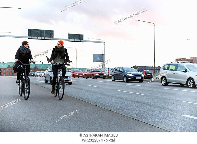 Happy man and woman talking while commuting on bicycles against sky