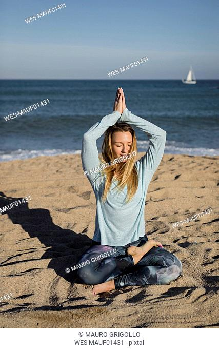 Woman doing yoga on the beach, lotus position