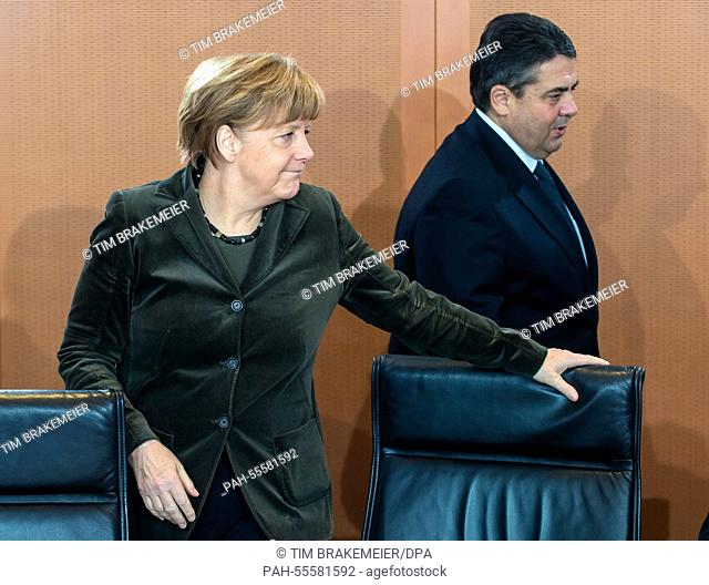German Chancellor Angela Merkel (CDU) and German Minister of Finance Sigmar Gabriel (SPD) arrive at the cabinet table in the Federal Chancellery in Berlin