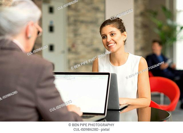 Young businesswoman and female colleague talking over office desk