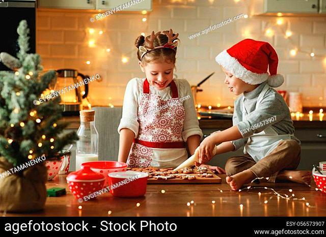 happy funny children boy and girl bake christmas cookies