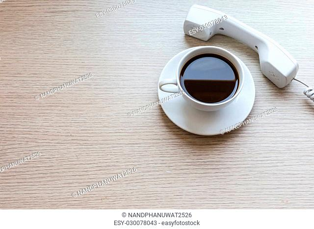 Top view white coffee cup and office phone on wooden table