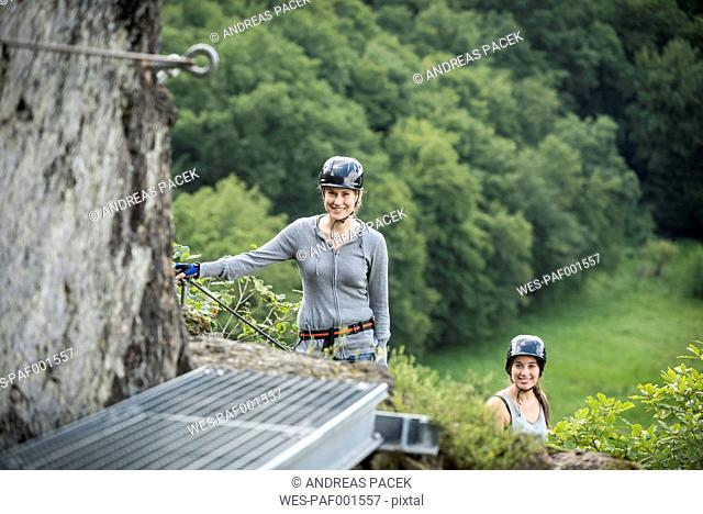 Germany, Westerwald, Hoelderstein, two smiling women climbing on via ferrata