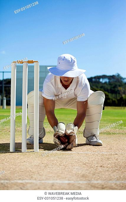 Full length of wicketkeeper holding ball behind stumps