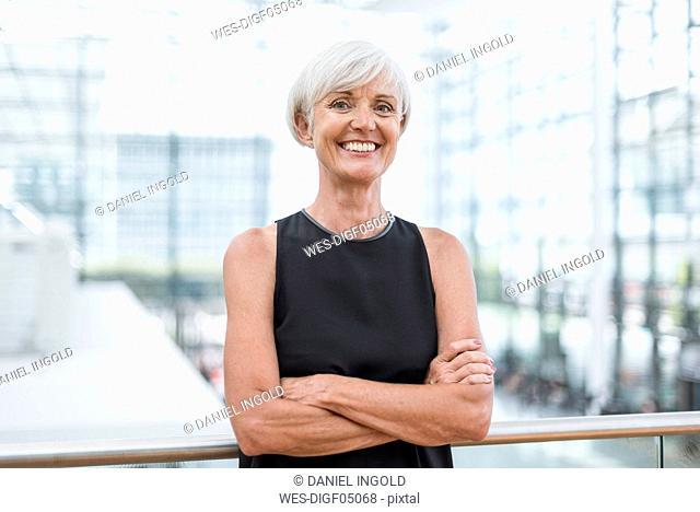Portrait of smiling senior woman wearing black dress