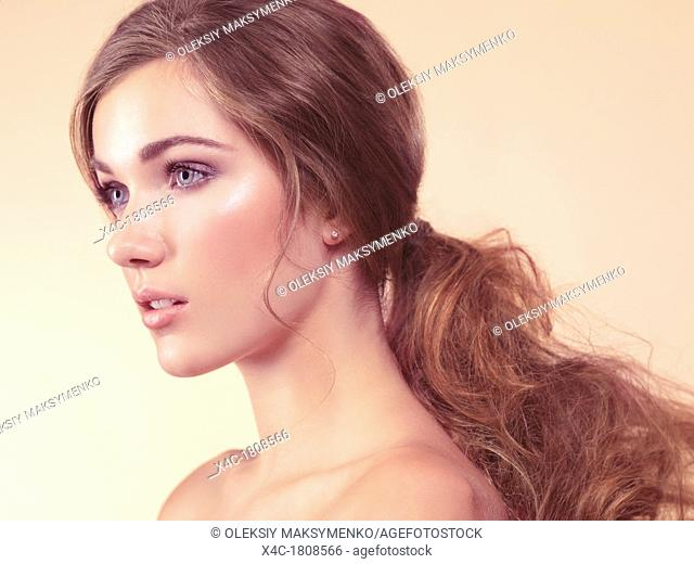 Beauty portrait of a young woman with soft natural look ond long hair in ponytail isolated on beige background