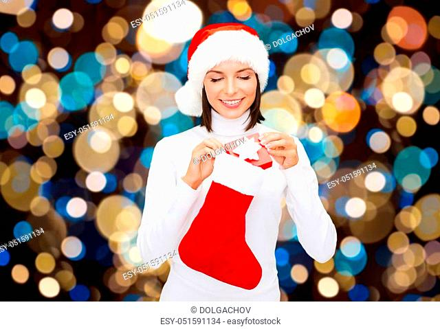 holidays, christmas and people concept - smiling woman in santa hat putting gift box into sock over lights background