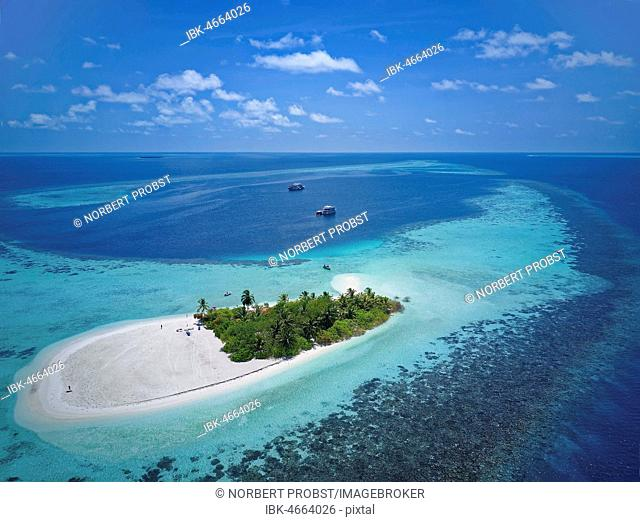 Uninhabited palm island, sandy beach all around, offshore coral reef, diving boat in the back, Ari atoll, Indian Ocean, Maldives