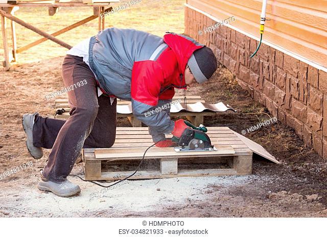 man saws a board with a circular saw