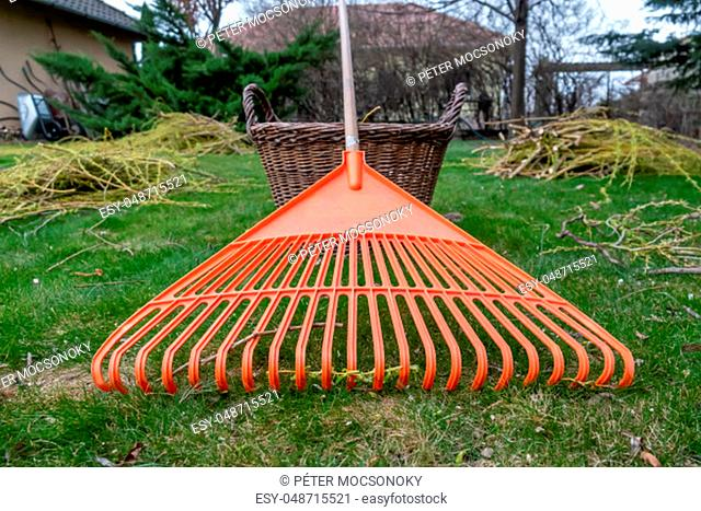 Orange rake next to a basket