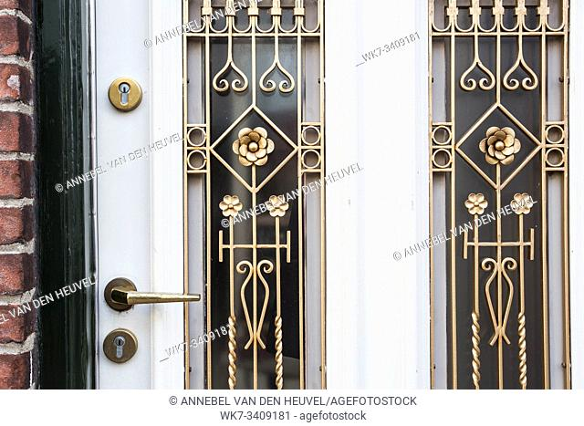 White front door with small square decorative windows close-up house decoration