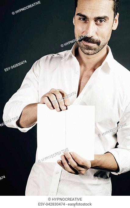 Young handsome man with beard and moustache showing a brochure against black background, studio portrait