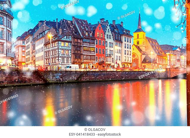 Picturesque Christmas quay and church of Saint Nicolas with mirror reflections in the river Ile during evening blue hour, Strasbourg, Alsace, France