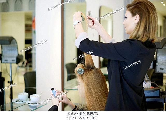 Hairdresser wrapping customer's hair in curlers in salon