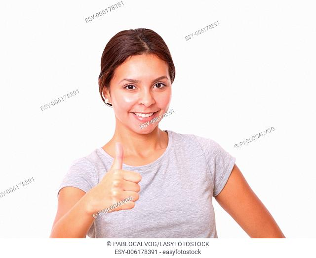 Portrait of charming young girl on grey t-shirt with ok sign smiling at you on isolated studio