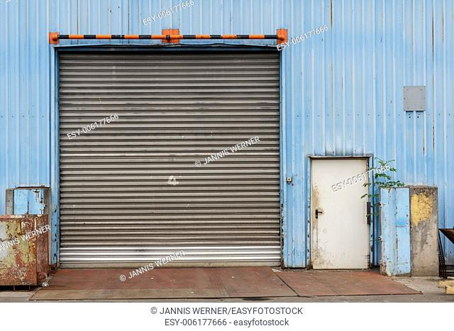 Closed gate in blue metal shed at industrial facility