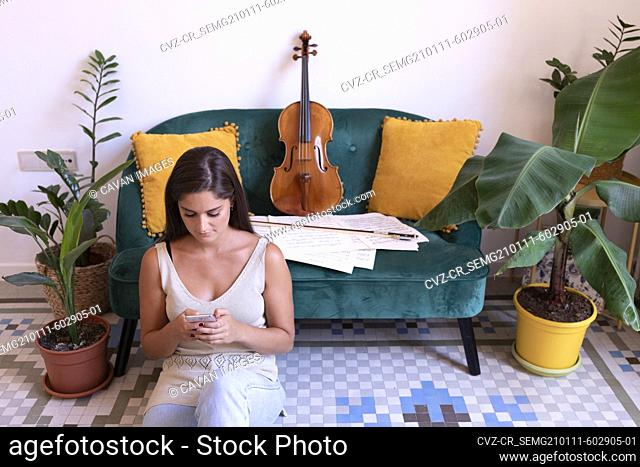 Young girl chatting on the floor, a viola is leaning on the sofa