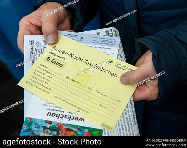 27 February 2020, Bavaria, Munich: A woman holds one of the first night taxi vouchers for women in the state capital in her hands