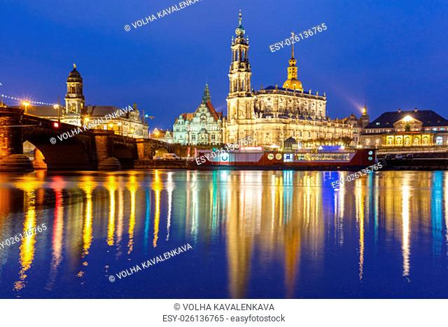Dresden Cathedral of the Holy Trinity aka Hofkirche Kathedrale Sanctissima Trinitatis and Augustus Bridge with reflections in the river Elbe at night in Dresden