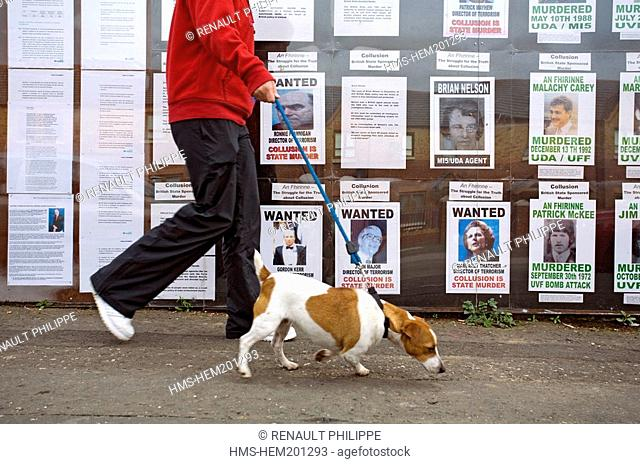 United Kingdom, Northern Ireland, Belfast, Catholic Falls area, walker and his dog passing in front of a public notice of Catholic victims killed by british...