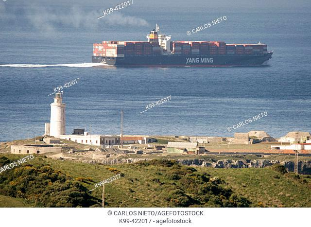 Containership crossing the Strait of Gibraltar and Pigeon Island lighthouse at fore, Tarifa. Cádiz province, Andalusia. Spain
