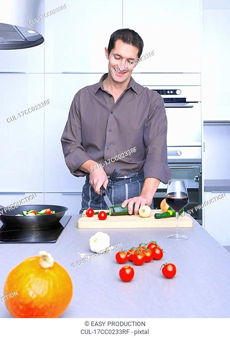 man cooking in a kitchen, and smiling