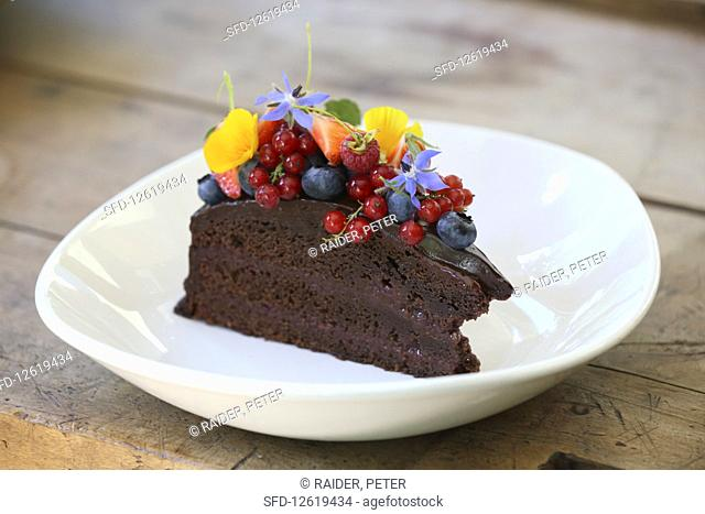 A piece of chocolate cake with berries and edible flowers
