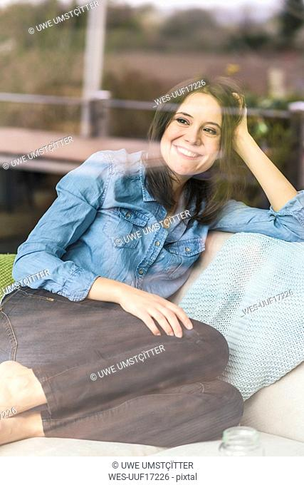 Portrait of happy woman behind windowpane at home