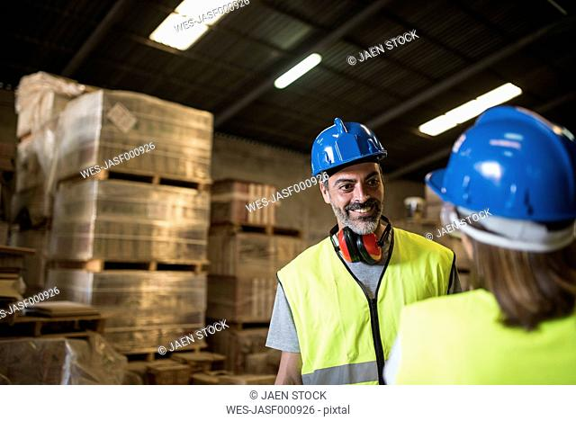 Man and woman dsicussing in warehouse of construction company