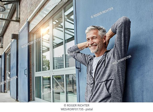 Portrait of laughing mature man in front of gym
