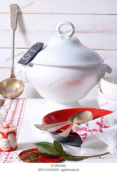 Classic soup terrine, a silver ladle, plates and cutlery