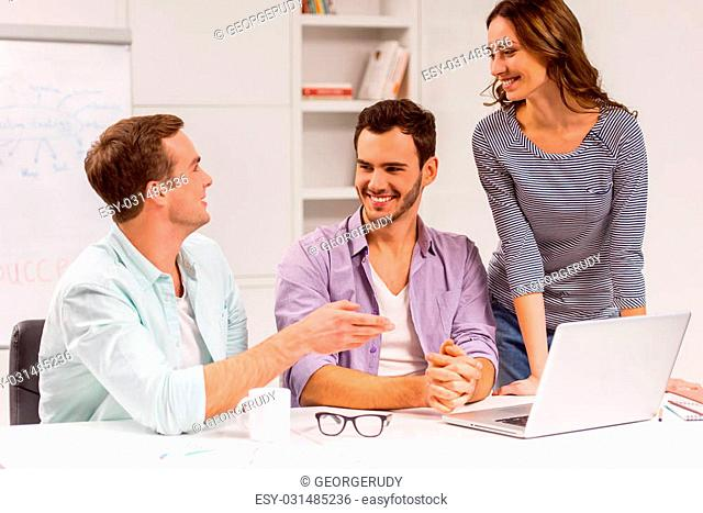 Two young attractive businessmen and one beautiful businesswoman in casual clothes using laptop, smiling and talking while working in office