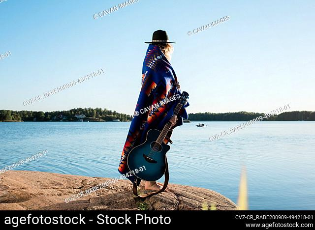 woman stood wrapped in a Pendleton blanket holding a guitar