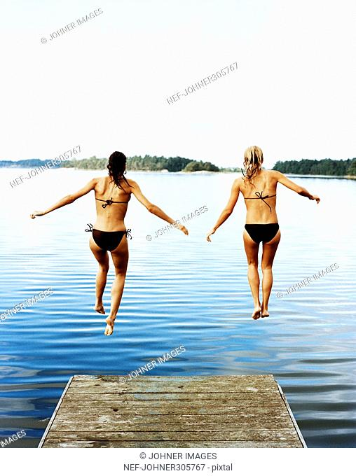 Two women jumping into the water