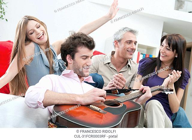 Joyful friends playing guitar at home