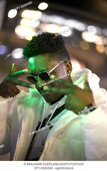 young African man posing with peace sign, V sign, in green lights at night, wearing sunglasses, cool attitude, in Munich, Germany