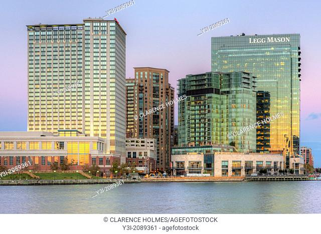 The orange colored western reflects in the windows of part of the skyline of the Harbor East development, including the Baltimore Marriott Waterfront Hotel and...