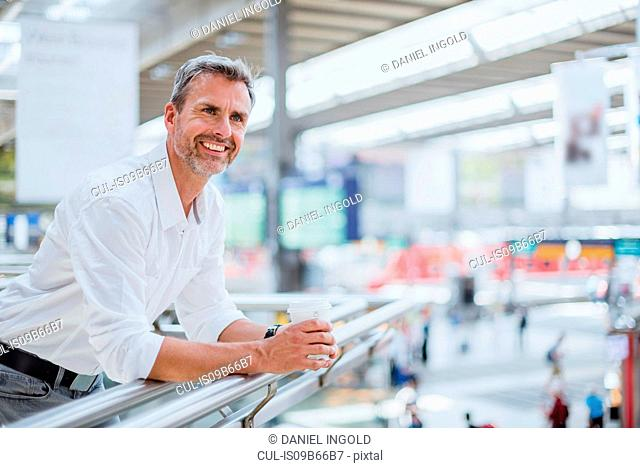 Portrait of mature man at train station, holding takeaway coffee cup